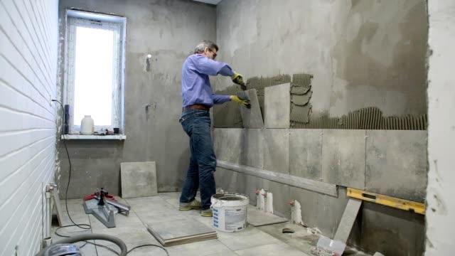 vídeos de stock, filmes e b-roll de instalação de telhas cerâmicas em uma casa de banho. - quadrado formato bidimensional