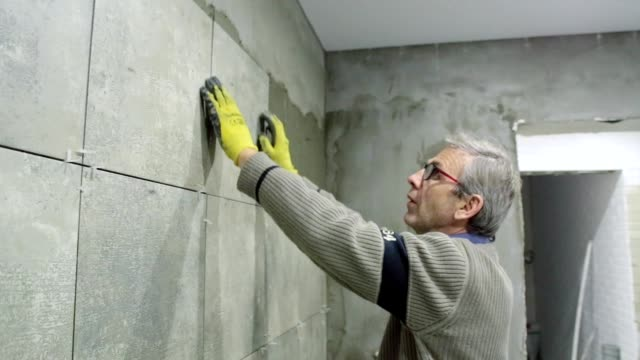 installation of ceramic tiles in a bathroom. - cement stock videos & royalty-free footage
