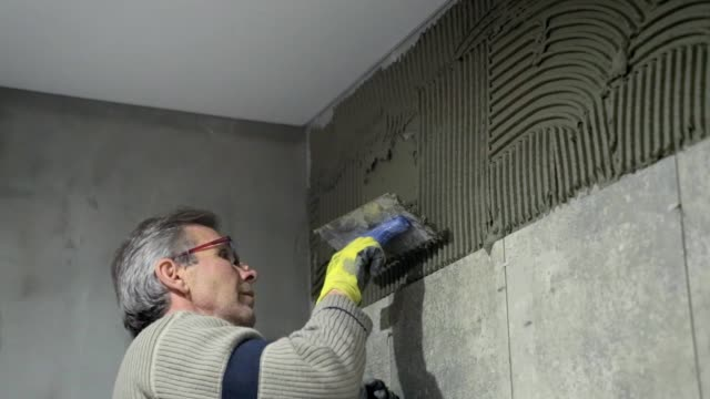 installation of ceramic tiles in a bathroom. - ukrainian ethnicity stock videos and b-roll footage
