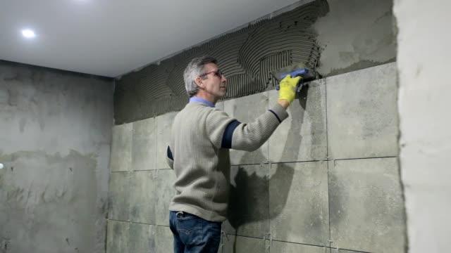 Installatie van keramische tegels in een badkamer.