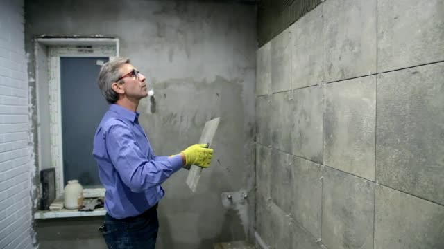 installation of ceramic tiles in a bathroom. - one mature man only stock videos & royalty-free footage
