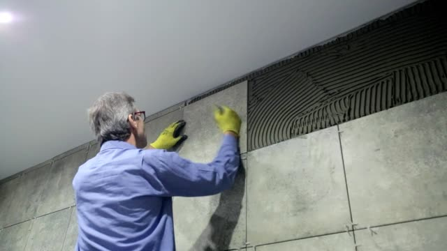 installation of ceramic tiles in a bathroom. - bathroom stock videos & royalty-free footage