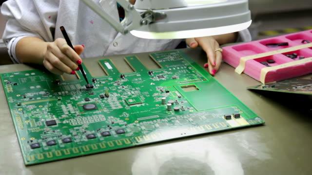 vidéos et rushes de installation de composant électrique sur circuit intégré - pince chirurgicale