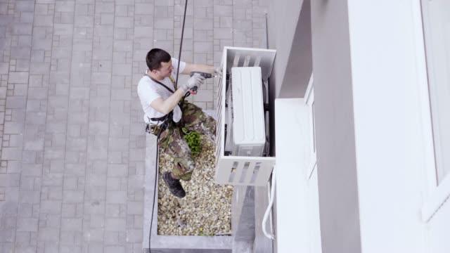 installation von klimaanlagen an einem gebäude im außenbereich - klimaanlage stock-videos und b-roll-filmmaterial