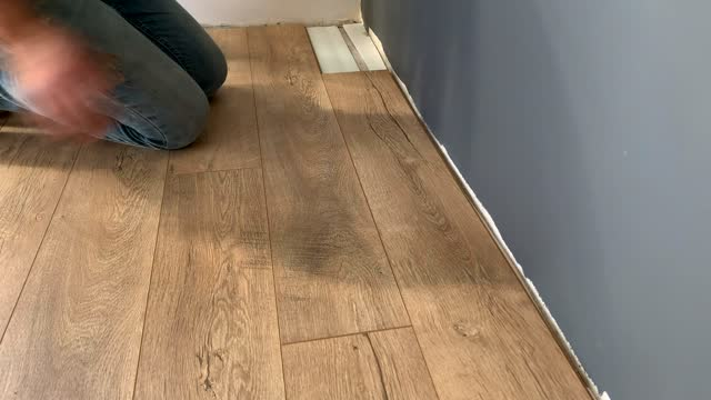 installing laminate floor, detail on man hands fixing one tile with hammer, over white foam base layer - new stock videos & royalty-free footage