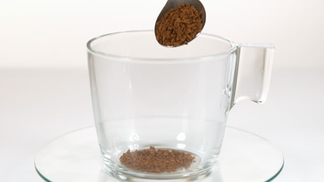 Instant Coffee Being Poured in a Cup against White Background, Slow motion
