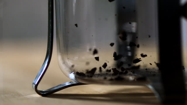 MS CU SLO MO Instant coffee flakes falling into glass cup