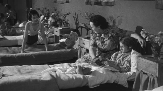 1950 ZO Institutionalized children lying on and making beds in dormitory / United Kingdom