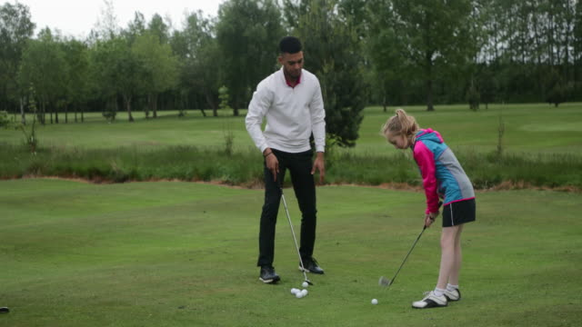 instructing a young female golfer - golf course stock videos & royalty-free footage