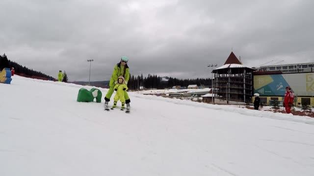 Kursleiter und Baby auf Skiern.