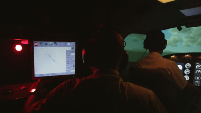 WS PAN instructor and pilots in professional flight simulator during flight, internal view, focus on instructor, RED R3D 4K