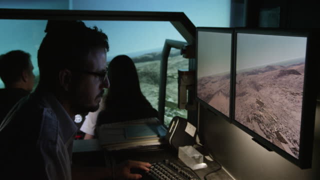 ws pan instructor and student pilots in helicopter flight simulator during simulated flight over mountainous terrain; focus remains on instructor throughout, red r3d 4k - air vehicle stock videos & royalty-free footage