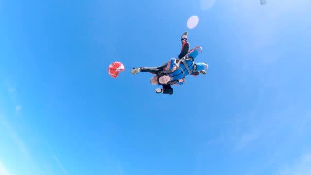 vidéos et rushes de l'instructeur et la femme sautent d'un avion avec un parachute. - sauter