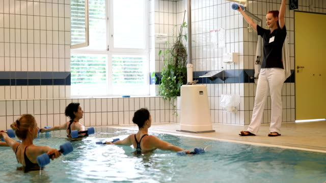 Instructor and women exercising at aqua gym