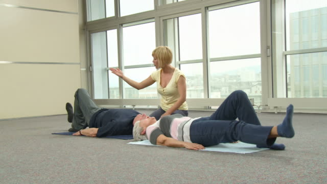 hd dolly: instructor assisting senior couple exercising - pilates stock videos and b-roll footage