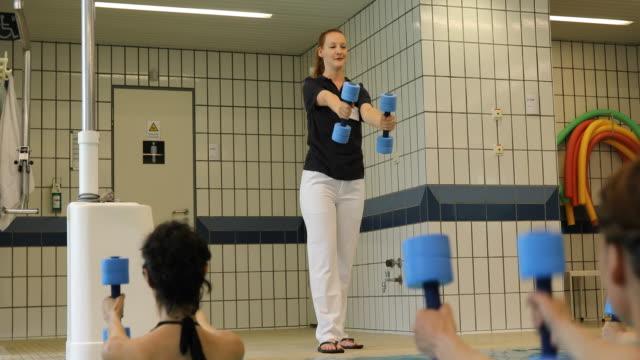 Instructor assisting women at aqua health club