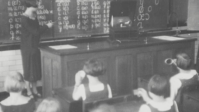 1925 montage instructor at blackboard with gramophone on desk teaching students languages, and schoolgirls using a stenciling roneograph machine and typewriters typing in business class at secondary school / newcastle upon tyne, england, united kingdom - 1925年点の映像素材/bロール