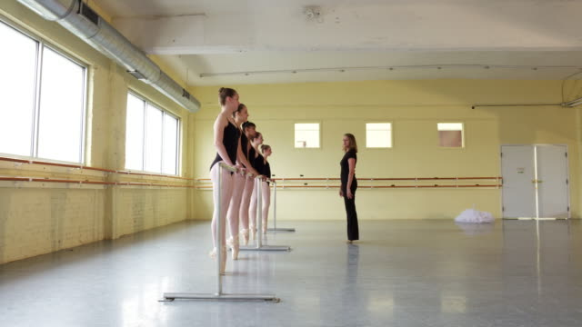 instructor coaching ballerinas at the barre - ballettstange stock-videos und b-roll-filmmaterial
