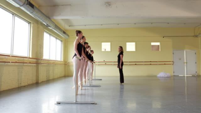 instructor coaching ballerinas at the barre - auf den zehenspitzen stock-videos und b-roll-filmmaterial