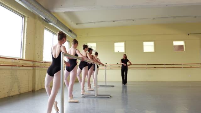 instructor coaching ballerinas at the barre - ballettstudio stock-videos und b-roll-filmmaterial
