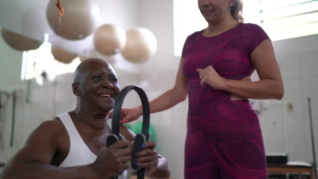 instructor doing physical therapy to senior woman - physical therapist stock videos & royalty-free footage