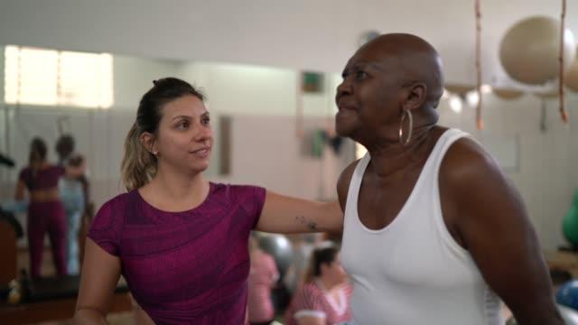 vídeos y material grabado en eventos de stock de instructor haciendo fisioterapia a una mujer mayor - equilibrio vida trabajo
