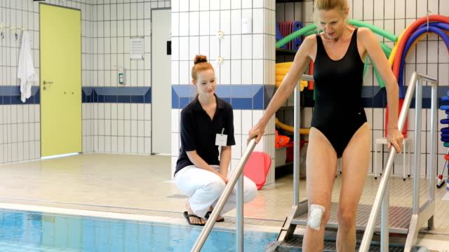 Instructeur bemoedigend gewonde vrouw aan aquagym