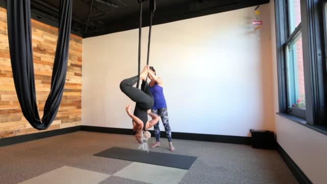 Instructor helping senior student in aerial silk yoga