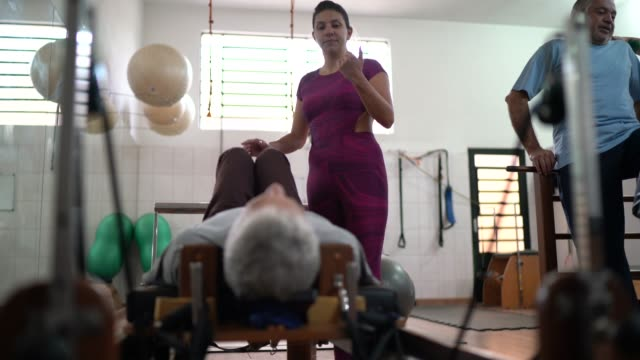 instructor helping student in physiotherapy exercise - chiropractic adjustment stock videos & royalty-free footage