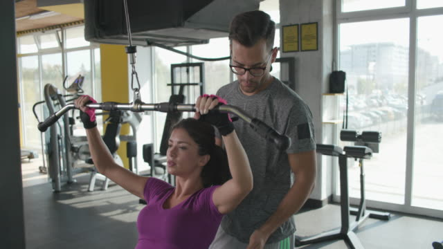 instructor helping woman with lateral pull-down weights exercise - lateral pull down weights stock videos & royalty-free footage