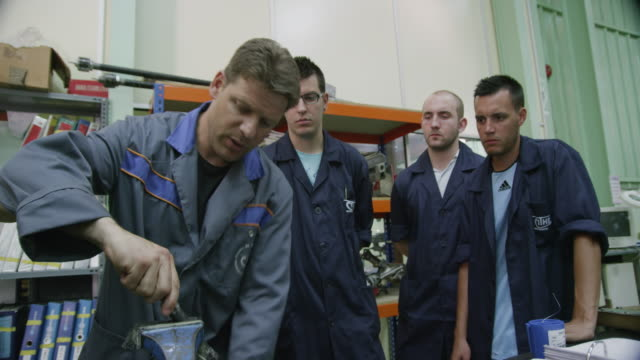 la ws instructor in a aviation mechanic training facility explaining something to a group of trainees, red r3d 4k - auszubildender stock-videos und b-roll-filmmaterial