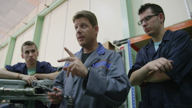 LA WS instructor in a aviation mechanic training facility explaining something to a group of trainees, RED R3D 4k