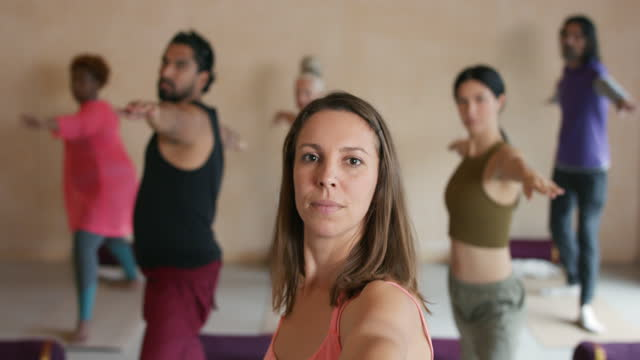 instructor leading class in stretching exercise in yoga studio - kent england stock videos & royalty-free footage