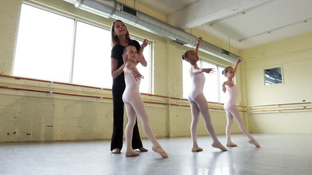 stockvideo's en b-roll-footage met instructor leading preteen ballerinas in practicing their form - trainer
