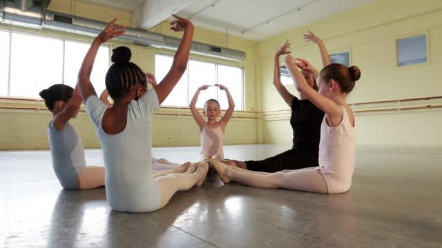 instructor leading preteen ballerinas in warm ups - böja sig bildbanksvideor och videomaterial från bakom kulisserna