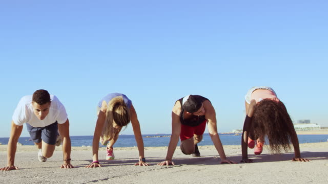 vídeos de stock e filmes b-roll de instructor motivating athletes exercising by beach - guidance