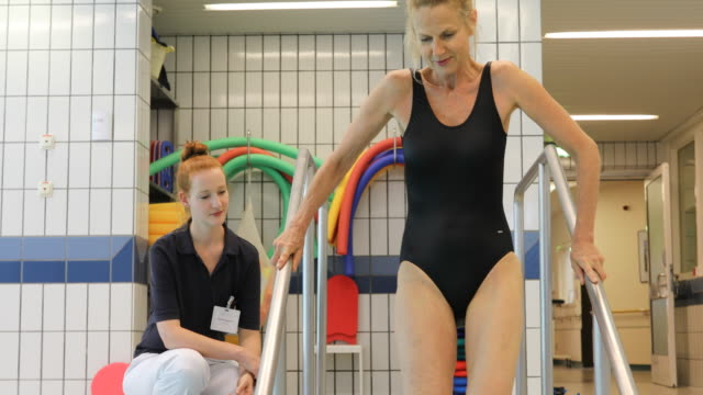Instructor motivating injured woman at aqua gym
