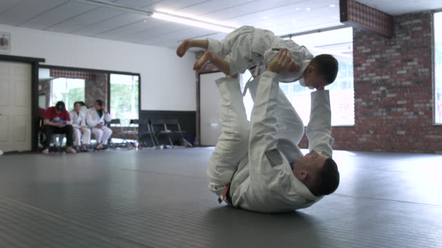 vídeos de stock e filmes b-roll de instructor practicing jiu-jitsu moves with a boy - artes marciais