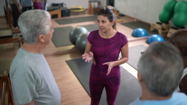 instructor talking to patients before starting exercises - chiropractic adjustment stock videos & royalty-free footage