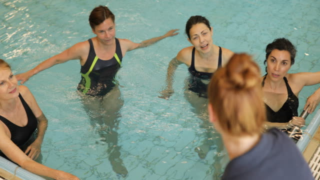 Instructor talking to women in swimming pool