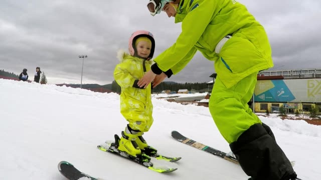a instructor teaches a little girl how to ski. - ski holiday stock videos & royalty-free footage
