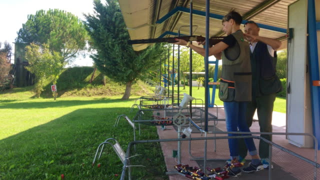 instructor teaching adult woman how to stand and aim with shotgun on shooting range - tiro al piattello video stock e b–roll