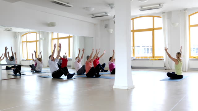 Instructor teaching senior people in yoga class