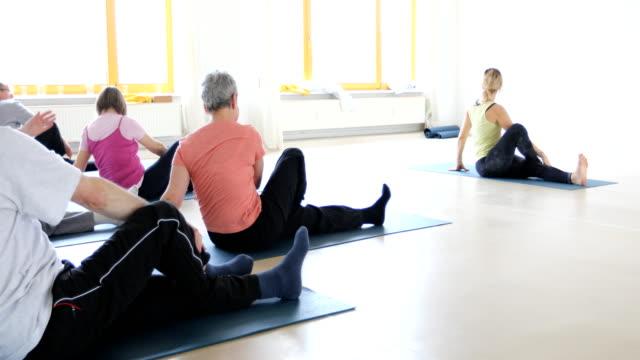 Instructor teaching senior people in yoga class