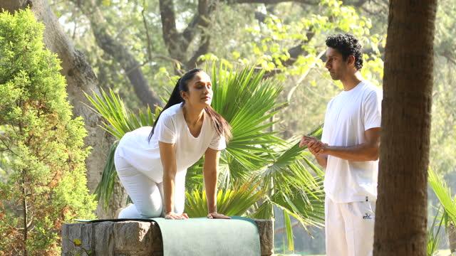 istruttore che insegna yoga posa alla donna al parco - vestito bianco video stock e b–roll