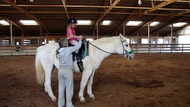 stockvideo's en b-roll-footage met ms instructor teaching young girl how to ride horse / lamy, new mexico, united states - recreatief paardrijden