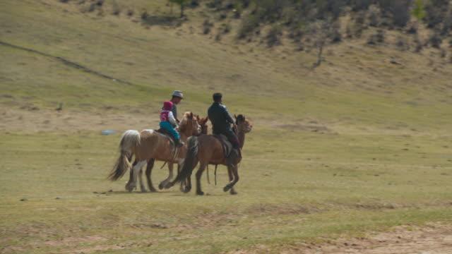 instructors and boy horseback riding on field during sunny day - ulaanbaatar, mongolia - ulan bator stock videos & royalty-free footage
