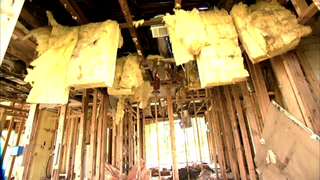insulation strips hanging from interior cross beams in damaged house zi ms ceiling fan w/ blades bent downward still attached to wooden beam... - ceiling fan stock videos & royalty-free footage