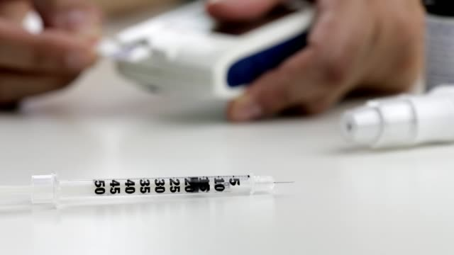 insulin syringe on foreground, blurred blood test on the background - type 1 diabetes stock videos & royalty-free footage