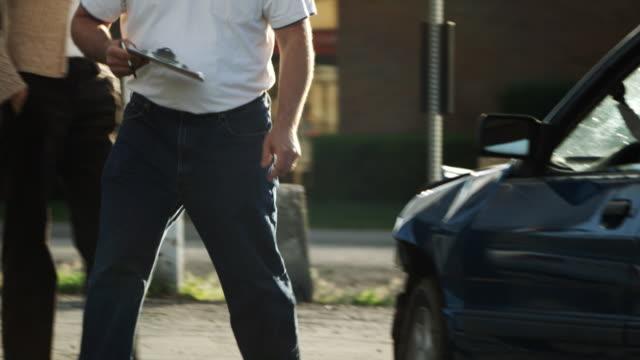 insurance adjuster looking at a car - ペイソン点の映像素材/bロール